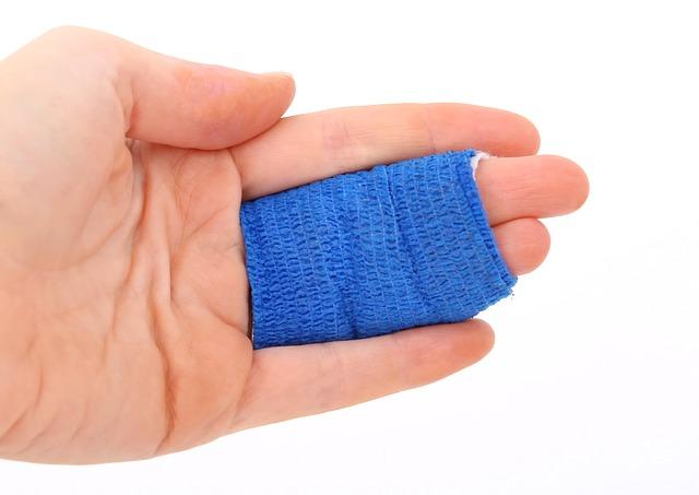 Lidská ruka, která má zraněné a obvázané dva prsty