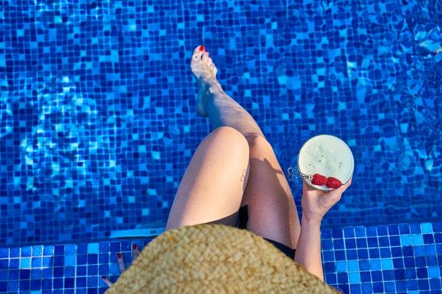 žena u bazénu s koktejlem